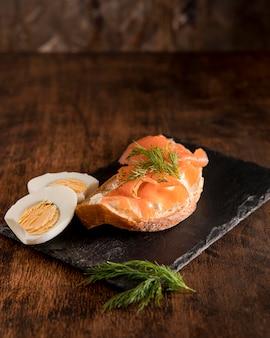 Angolo alto del panino sull'ardesia con salmone e uovo sodo