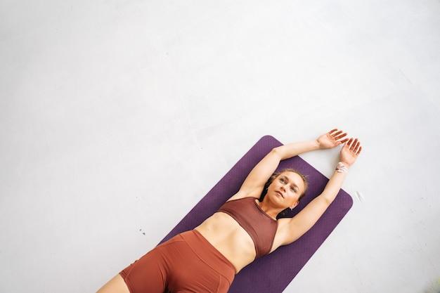Colpo ad alto angolo di una giovane donna in forma con un corpo atletico perfetto che indossa abbigliamento sportivo che si allena sdraiato sul tappetino da allenamento. concetto di stile di vita sano e attività fisica a casa.