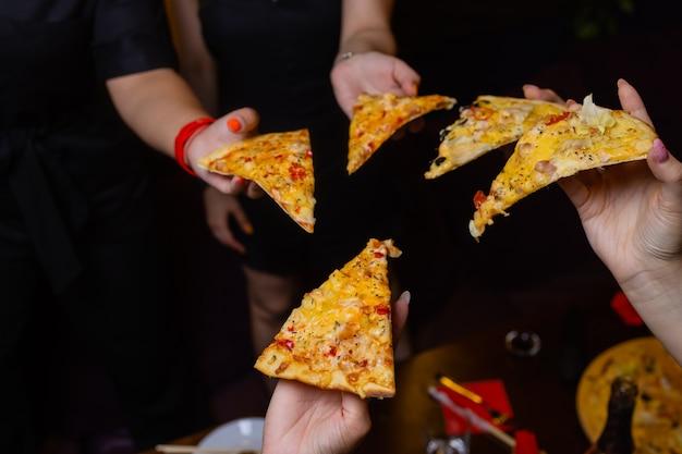 Inquadratura dall'alto di un gruppo di mani di persone irriconoscibili che afferrano ciascuna una fetta di pizza.