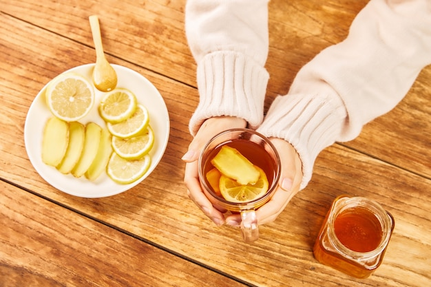 Colpo ad alto angolo delle mani che tengono una tazza di tè con limoni, zenzero e miele sul tavolo