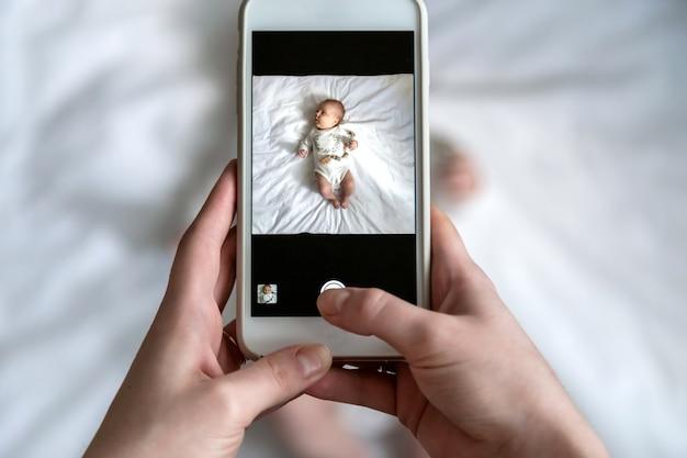 Sopra l'angolo alto sparato della mamma felice che prende a foto il suo neonato o ragazza a letto con uno smartphone a casa