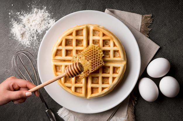 Alto angolo di ripresa di una persona che fa i waffle con miele in una cucina