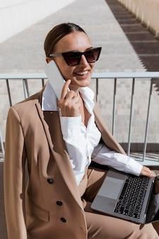 Donna di smiley di alto angolo che parla sul telefono