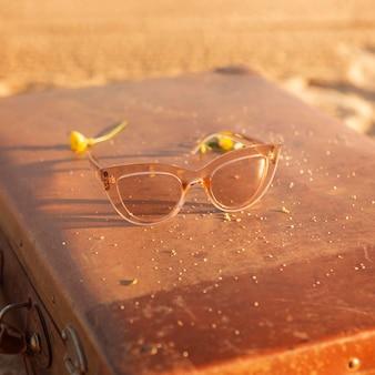 Occhiali da sole ad alto angolo sulla valigia in spiaggia