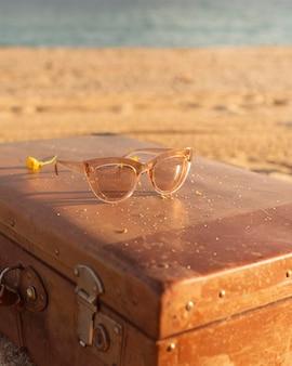 Occhiali da sole ad alto angolo sulla valigia in riva al mare