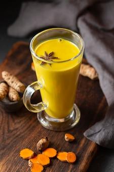Bicchiere alto angolo alto con bevanda gialla e anice stellato