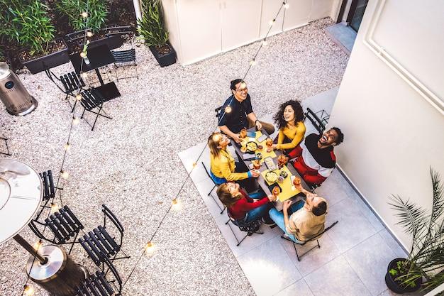 Vista dall'alto di alto angolo di amici felici che bevono cocktail e si divertono alla festa in giardino del ristorante Foto Premium