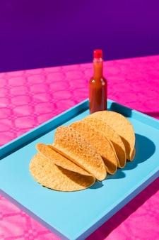 Tortillas ad angolo alto e bottiglia di salsa sul vassoio