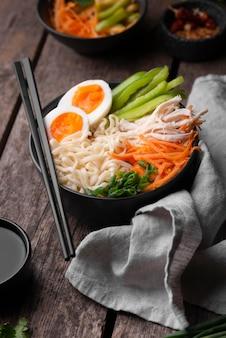 Alto angolo del piatto asiatico tradizionale con bacchette e tagliatelle