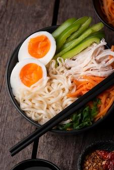 Alto angolo del piatto asiatico tradizionale con le uova nelle tagliatelle