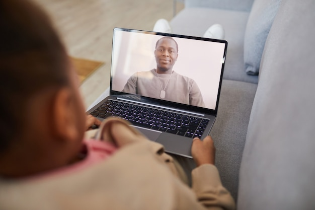 Veduta dall'alto di una ragazza afro-americana che parla con papà tramite chat video mentre si allontana socialmente, copia spazio