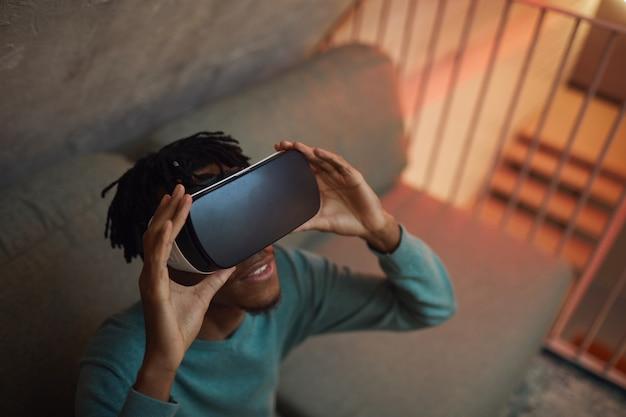 Veduta dall'alto di un uomo afro-americano che indossa attrezzatura vr mentre si gode un'esperienza coinvolgente in interni futuristici