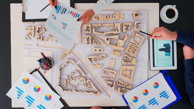 Vista ad alto angolo di architetti con edifici prototipi di dispositivi digitali e tablet seduti al tavolo in ufficio per conferenze, pianificazione del prossimo progetto
