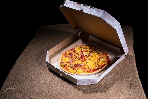 Vista ad alto angolo di pizza artigianale condita con varietà di condimenti e formaggio in scatola di cartone da asporto con coperchio aperto sulla superficie del tavolo con spazio di copia