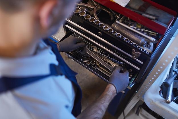Elevato angolo di visione al meccanico di automobili scegliendo gli strumenti durante la riparazione del veicolo in garage, copia dello spazio