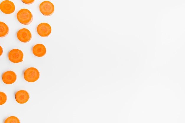 Vista dell'angolo alto delle fette della carota su superficie bianca