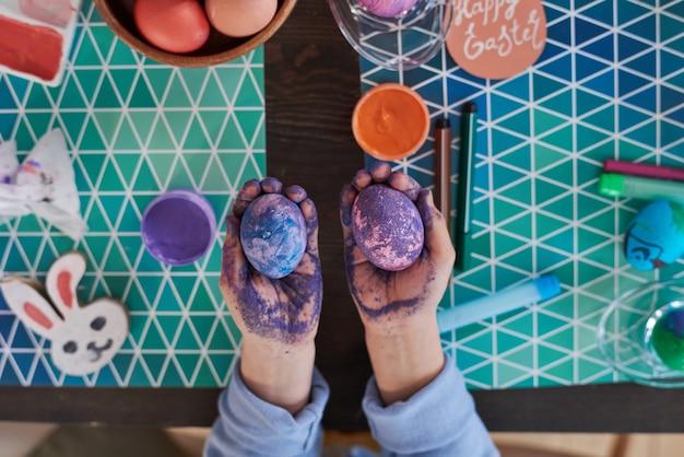 Vista dall'alto del bambino che tiene in mano le uova dipinte, le colora con una tecnica speciale