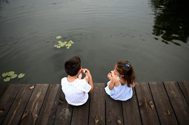 Veduta dall'alto dei bambini sul molo con i piedi abbassati nel lago, spruzzi d'acqua, mangiare anguria all'aperto. concetto di vacanze estive di campagna.