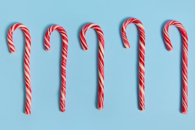 Veduta dall'alto della decorazione di natale. composizione piatta di cinque bastoncini di zucchero dolci, lecca-lecca di natale sdraiati su sfondo blu con spazio copia per la pubblicità