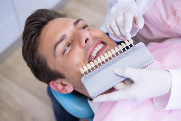 Vista di alto angolo del dentista che tiene attrezzatura durante l'esame del paziente