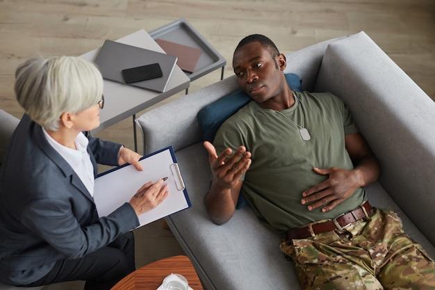 Veduta dall'alto del soldato depresso e del suo psicoterapeuta durante una sessione