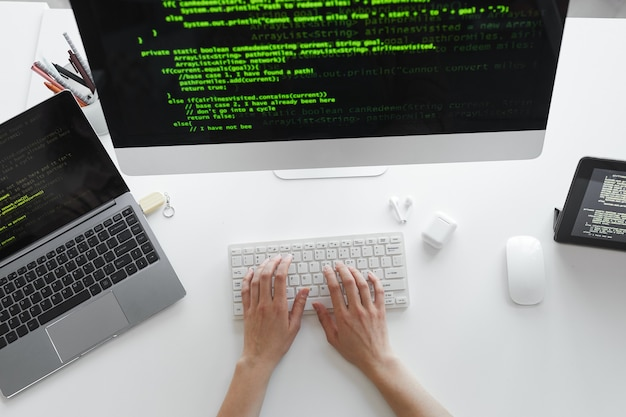 Elevato angolo di visione dello sviluppatore che digita sulla tastiera del computer che installa il nuovo sistema sul computer al tavolo