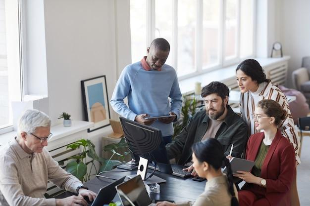 Vista ad alto angolo di diversi gruppi di uomini d'affari che si incontrano in ufficio e usano il computer mentre discutono del progetto