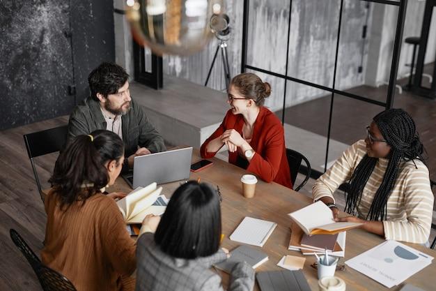 Vista dall'alto in un gruppo eterogeneo di uomini d'affari che si incontrano a tavola in eleganti interni di uffici, spazio di copia