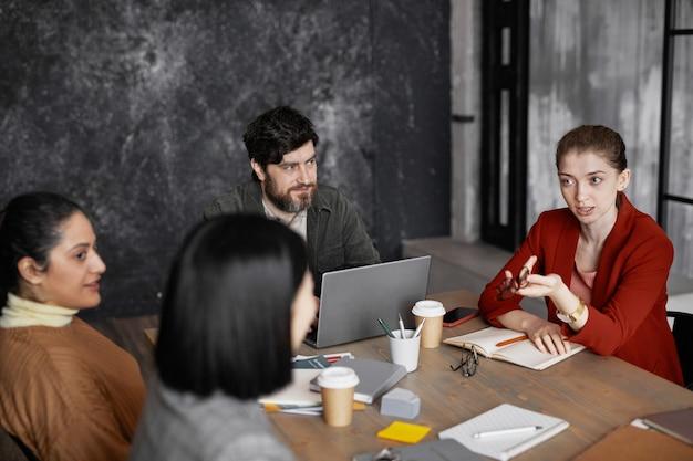 Vista dall'alto in un gruppo eterogeneo di uomini d'affari che si incontrano a tavola, si concentrano su giovani donne d'affari che indossano una giacca rossa e condividono idee