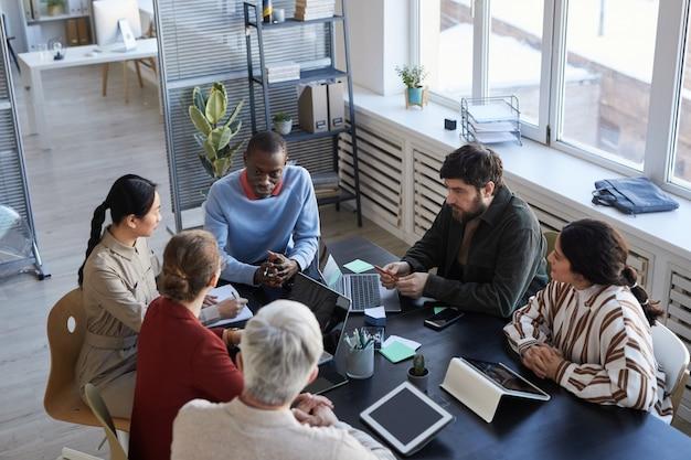 Vista dall'alto in un gruppo eterogeneo di uomini d'affari al tavolo durante la riunione informativa in ufficio, concentrarsi sull'uomo afroamericano sorridente