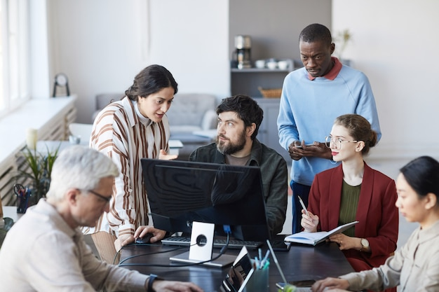 Vista ad alto angolo di diversi gruppi di persone che lavorano insieme in ufficio e utilizzano il computer mentre discutono del progetto