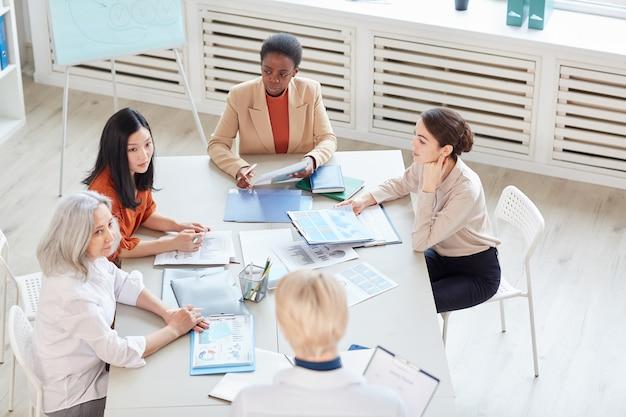 Veduta dall'alto al gruppo eterogeneo di imprenditrici di successo che discutono del progetto mentre è seduto al tavolo durante la riunione nel moderno ufficio bianco