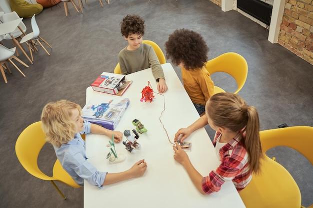 Vista dall'alto di diversi bambini seduti al tavolo che esaminano giocattoli tecnici pieni di dettagli