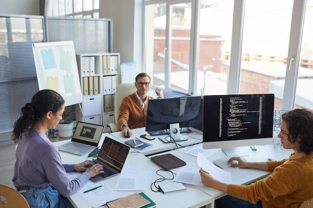 Vista dall'alto in un team di sviluppo software diversificato che utilizza computer e scrive codice mentre si collabora al progetto in un ufficio moderno, spazio di copia