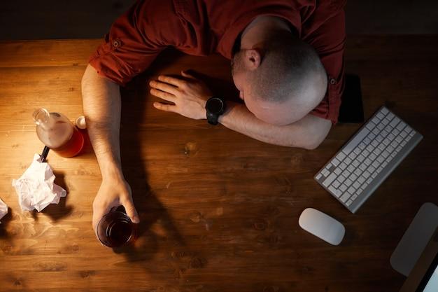 Veduta dall'alto di un uomo ubriaco che dorme sul posto di lavoro davanti al computer
