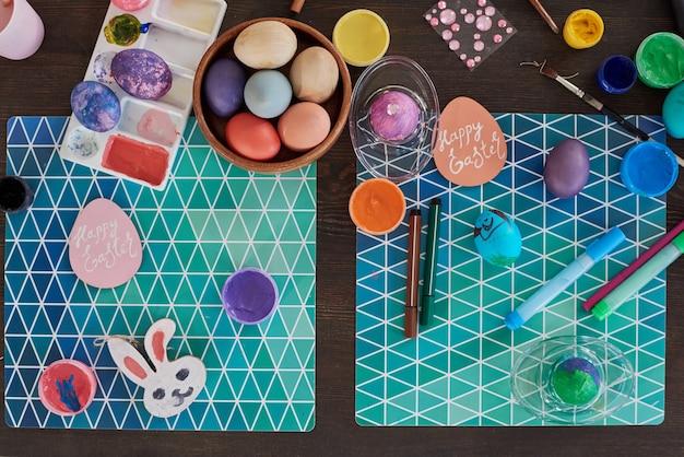 Vista dall'alto del biglietto di auguri e delle uova dipinte sul tavolo che si preparano per la pasqua