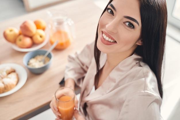 Vista dall'alto di una bella donna felice con un sorriso stupendo seduto al tavolo della colazione con un bicchiere di succo d'arancia fresco nelle mani