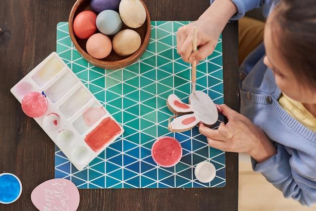 Veduta dall'alto della bambina che fa artigianato per le vacanze di pasqua e dipinge le uova al tavolo