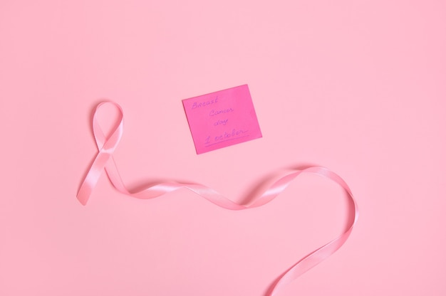 Vista ad alto angolo di un lungo nastro rosa con un'estremità infinita e una nota di carta con scritta 1 ottobre consapevolezza del cancro al seno, isolata su sfondo rosa con spazio di copia. lay piatto