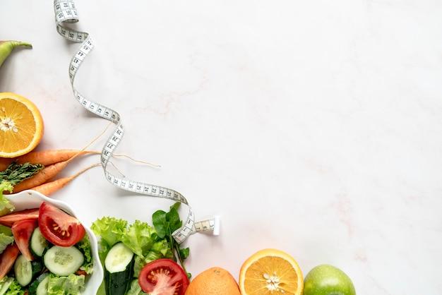 Vista dell'angolo alto del nastro di misurazione vicino alle verdure e ai frutti organici sopra fondo bianco
