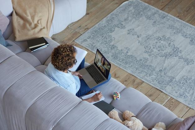 Vista ad alto angolo di una ragazza adolescente di razza mista che usa il laptop mentre fa una lezione video online con una donna