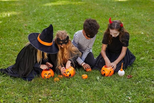 Veduta dall'alto al gruppo multietnico di bambini che indossano costumi prendendo caramelle da secchi di halloween all'aperto, copia dello spazio