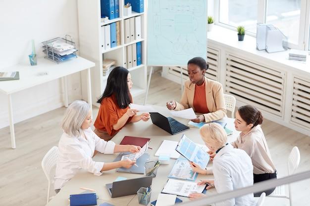 Veduta dall'alto al gruppo multietnico di imprenditrici di successo che discutono del progetto mentre era seduto al tavolo durante la riunione nel moderno ufficio bianco