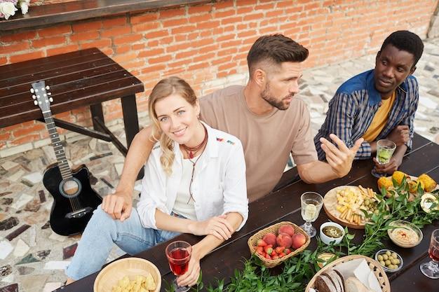 Veduta dall'alto al gruppo multietnico di giovani che godono della cena all'aperto