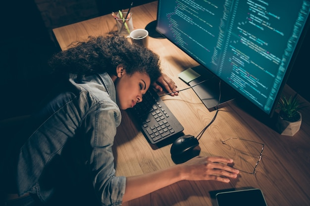 La foto di vista dell'angolo alto della signora di affari si è addormentata vicino al monitor