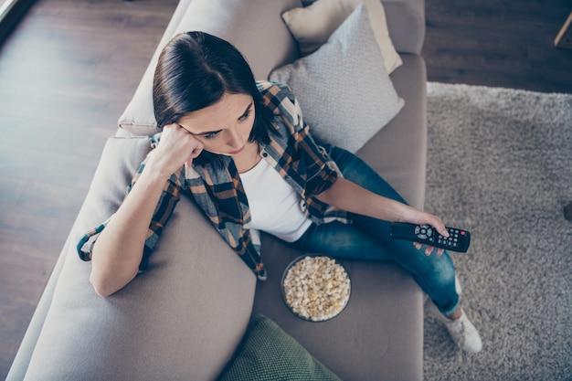 Vista di alto angolo foto della bella signora che tiene il telecomando e piatto di popcorn sconvolto del finale seriale preferito seduto sul divano indossando abiti casual appartamento al chiuso