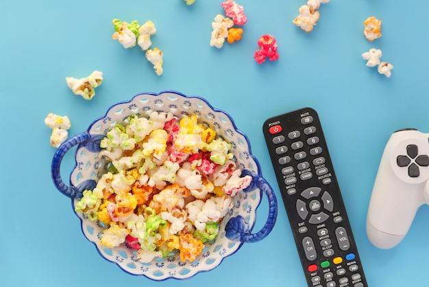 Vista dall'alto di popcorn, joystick e telecomando tv su sfondo blu