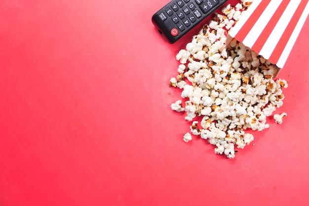 Veduta dall'alto di popcorn e telecomando della tv su sfondo rosso.