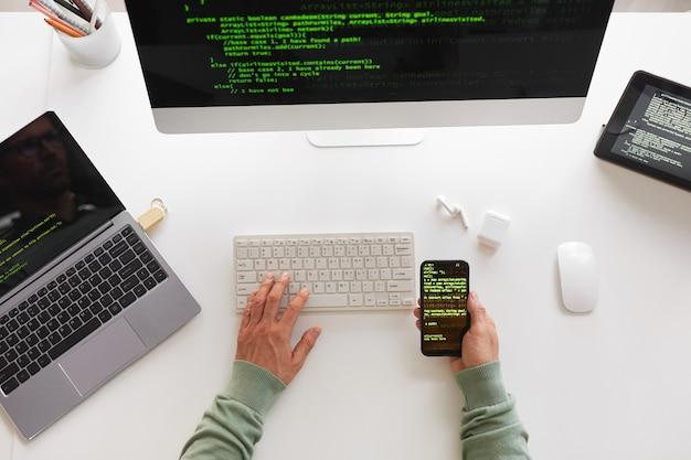 Veduta dall'alto del programmatore seduto al tavolo utilizzando il computer portatile e il design del sito web di programmazione del telefono cellulare