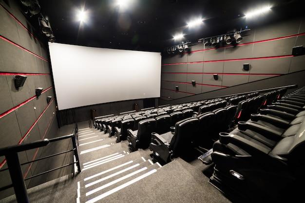 La vista dell'angolo alto dello schermo e le file delle sedie rosse comode illuminano il cinema rosso della stanza